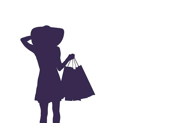 買い物袋を保持しているシルエット女性。販売と割引の概念 Premiumベクター