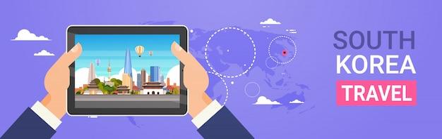 Южная корея путешествия достопримечательности руки держат цифровой планшет с пейзажем сеула Premium векторы