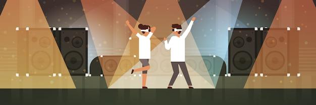 ダンサーカップル光効果ディスコスタジオ音楽機器マルチメディアスピーカーとステージで踊る仮想現実の眼鏡を着用 Premiumベクター