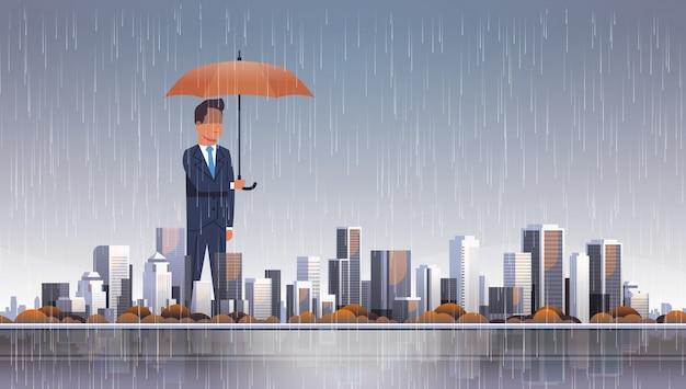 嵐で傘を保持している実業家 Premiumベクター