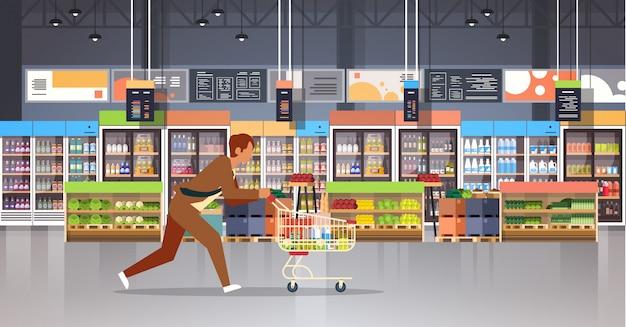 ショッピングトロリーでビジネスの男性顧客を実行 Premiumベクター