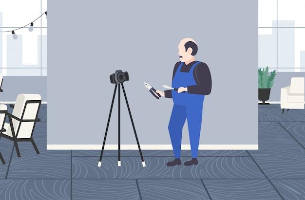 Разнорабочий рабочий с отверткой и плоскогубцы блоггер записи онлайн видео с цифровым фотоаппаратом на штатив социальной сети блогов концепция современной квартиры интерьер полная длина горизонтальный Premium векторы