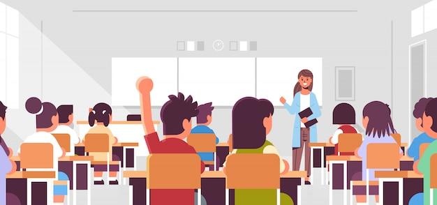 生徒グループが教室で教える教育コンセプトモダンなクラスの部屋のインテリアの中に教室で答えるために手を上げる女教師男子生徒に聞く Premiumベクター