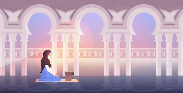 ラマダンカリームの聖なる月の宗教概念の中に読書コーランを祈って宗教的なイスラム教徒の女性 Premiumベクター