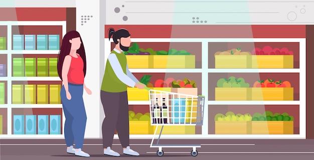 食料品とトロリーカートを押してカップル肥満男性女性一緒に買い物肥満不健康なライフスタイルコンセプトモダンな食料品店のインテリアフルレングスフラット水平 Premiumベクター