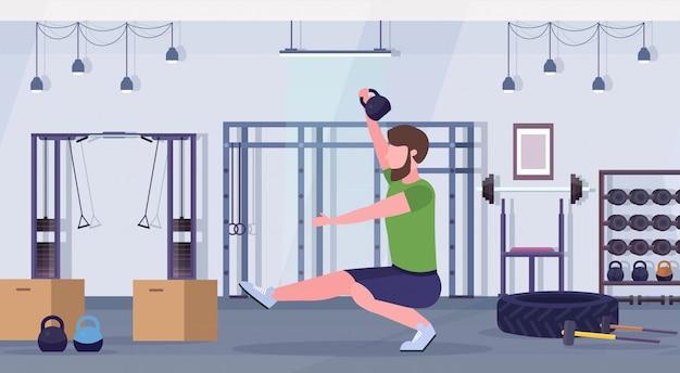 Спорт человек делает приседания упражнения с гирями парень тренировка кардио тренировки концепция современный тренажерный зал клуб здоровья интерьер горизонтальный полная длина Premium векторы