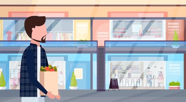 衣料品店やコーヒーショップのスーパーインテリア水平肖像フラットでモダンな小売モールを歩いて食料品の男性の漫画のキャラクターの買い物袋を運ぶ男 Premiumベクター