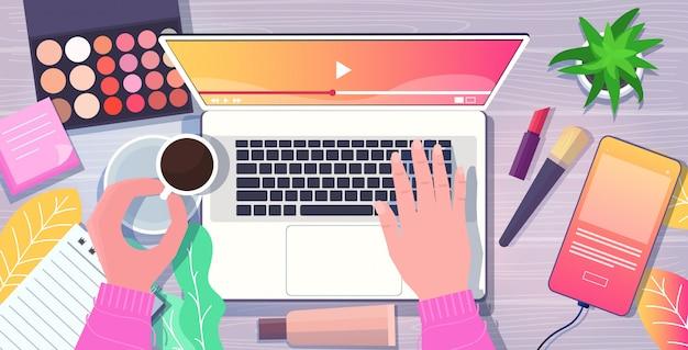 Красота блоггер руки, используя ноутбук на рабочем месте смартфон косметика кофейная чашка на столе социальные медиа сети блог концепция верхний угол зрения горизонтальный вид Premium векторы