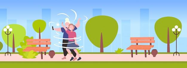 Толстые и худые женщины пара, принимая селфи фото на смартфон камеры девушки стояли вместе ожирение концепция городской парк городской пейзаж фон горизонтальный полная длина Premium векторы