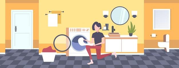 Женщина кладет грязную одежду в стиральную машину домохозяйка делает работу по дому современная прачечная интерьер мультипликационный персонаж полная длина горизонтальный Premium векторы