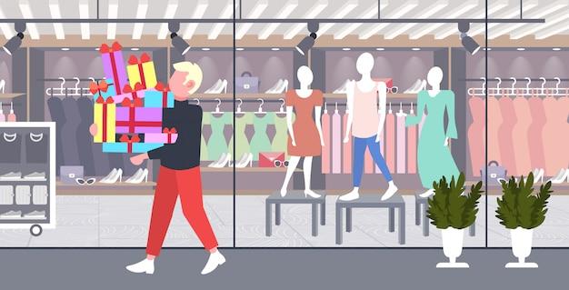 Человек, несущий стопку обернутых подарочных коробок большая сезонная распродажа шоппинг концепция парень держит разноцветные подарки современный бутик модный магазин экстерьер полная длина горизонтальный Premium векторы