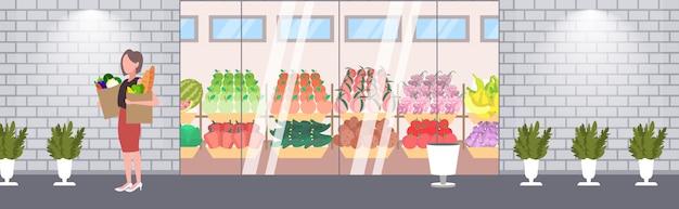 Женщина покупатель держа бумажные мешки полные бакалеи женщина покупатель покупка продуктов покупка концепция современный продуктовый магазин супермаркет экстерьер полная длина горизонтальный баннер Premium векторы