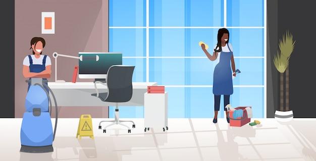 掃除機とぼろきれを使用して女性の掃除機が制服一緒に働くレース用務員チームクリーニングサービスコンセプトモダンなオフィスインテリア水平全長ベクトルイラスト Premiumベクター