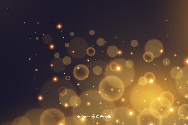 金色の粒子のボケ味の装飾的な背景 無料ベクター