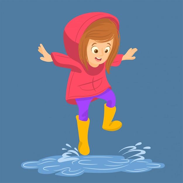 防水コートの少女は水たまりにジャンプします Premiumベクター
