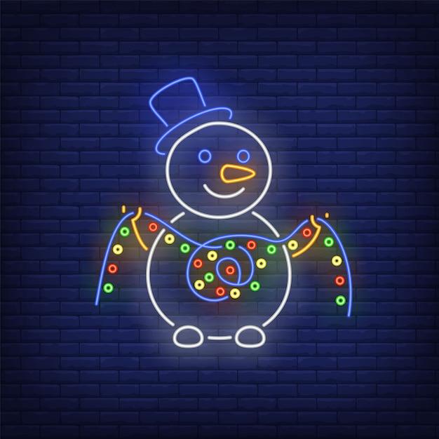 Снеговик в шляпе топпер и держит огни гирлянды в неоновом стиле Бесплатные векторы