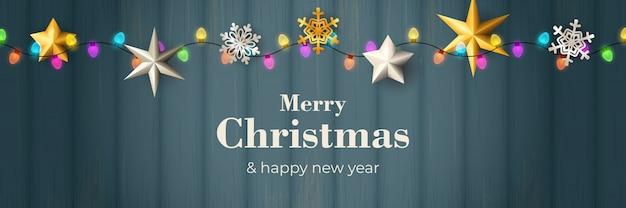 Счастливого рождества баннер с гирляндой на синем деревянном основании Бесплатные векторы