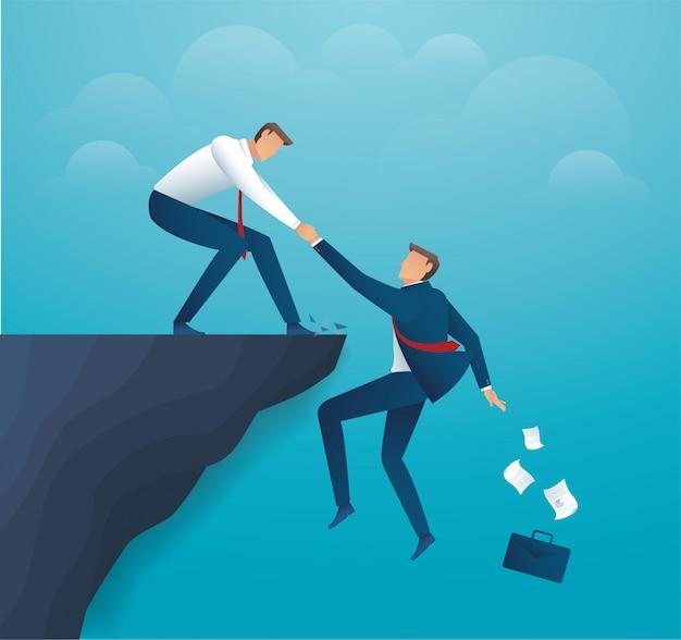 崖にぶら下がっているパートナーの手を繋いでいる男 Premiumベクター