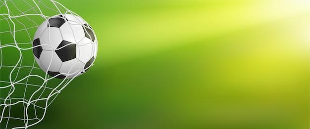 緑色の背景でゴールにサッカーボール Premiumベクター