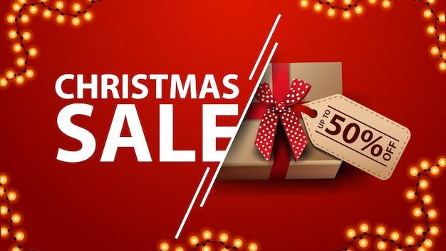 Рождественская распродажа красный скидка баннер с гирляндой и подарок с луком и ценником Premium векторы