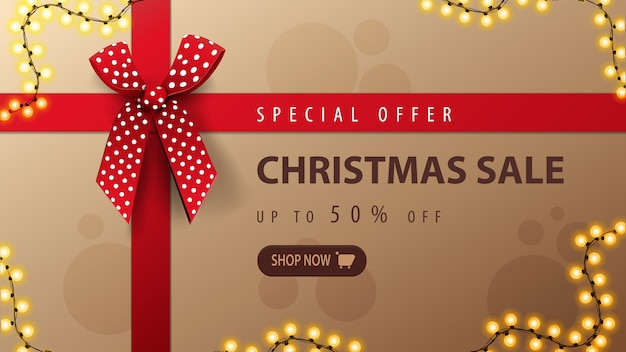 特別オファー、クリスマスセール、赤いリボンと弓、トップビューでクリスマスプレゼントボックスの形で割引バナー Premiumベクター