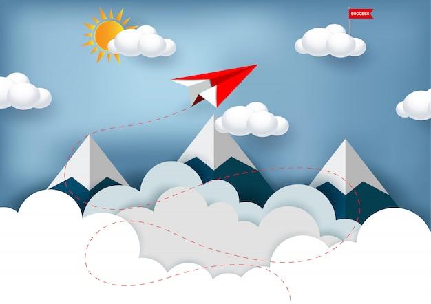 赤い紙飛行機は山の上を飛んでいる間雲の上の赤い旗ターゲットに飛んでいます。 Premiumベクター