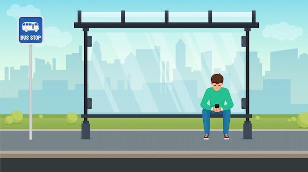 Молодой человек сидит в одиночестве на автобусной остановке и с помощью своего телефона. иллюстрации. Premium векторы