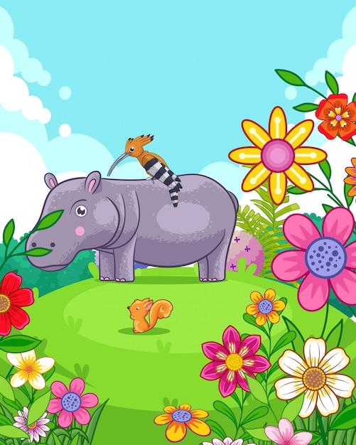 Счастливый милый бегемот с цветами, играя в саду Premium векторы