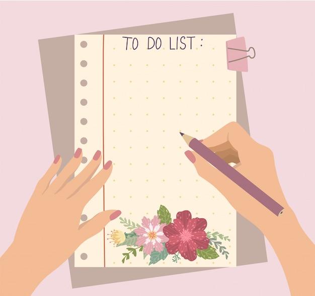 女性の手が美しい花のメモ帳で鉛筆を保持します。 Premiumベクター