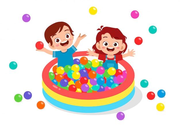 幸せなかわいい子供たちがボール風呂プールをプレイ Premiumベクター