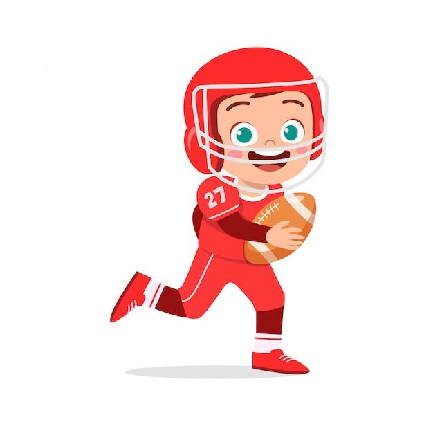 幸せなかわいい子供男の子がアメリカンフットボールをプレイ Premiumベクター
