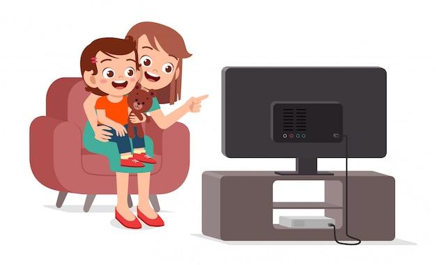 Счастливый милый ребенок смотреть телевизор с семьей вместе Premium векторы