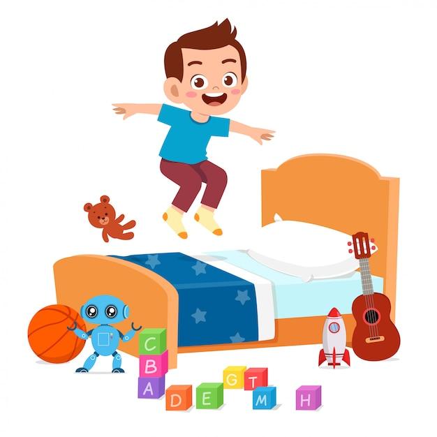 Счастливый милый маленький ребенок мальчик прыгать на кровати Бесплатные векторы