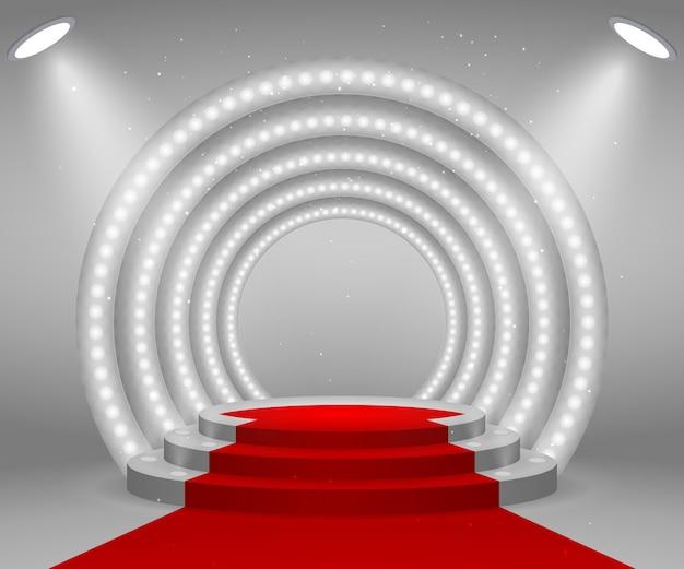 表彰式のためのライトが付いている段階。レッドカーペットで照らされたラウンド表彰台。ペデスタル。 Premiumベクター
