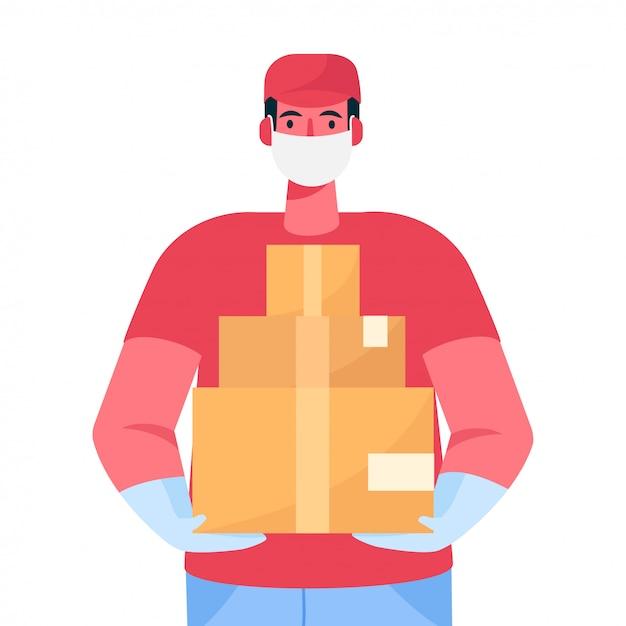 Курьер в защитной медицинской маске и перчатках держит в руках картонные коробки Premium векторы