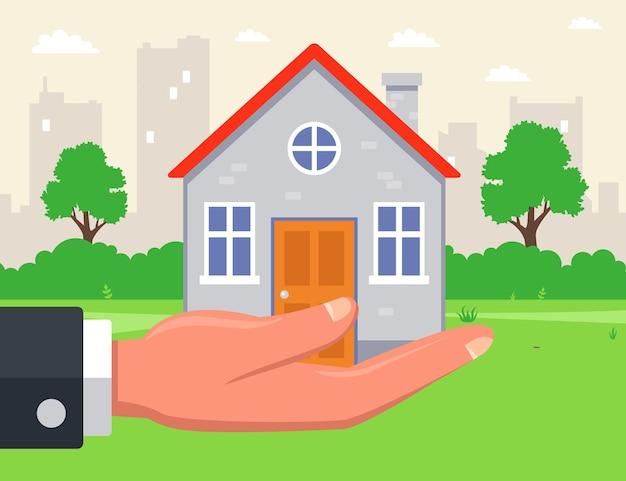 男は街を背景に手に家を持っています。郊外の不動産の売却。図。 Premiumベクター