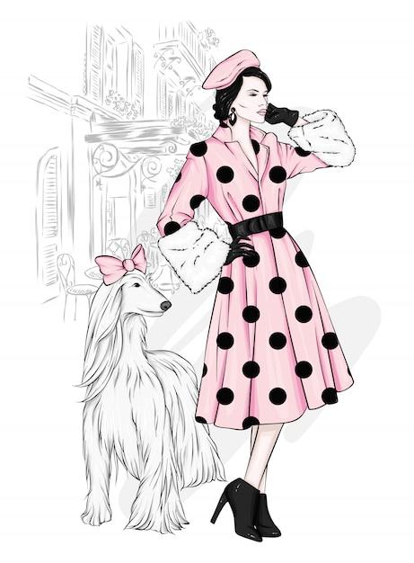 コートとブーツで美しい犬と背の高いスリムな女の子。 Premiumベクター