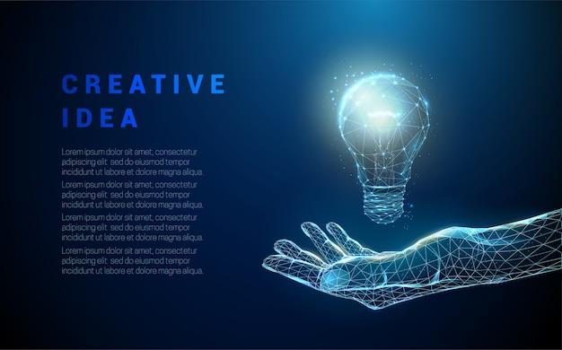 電球を持っている抽象的な手。低ポリスタイルのデザイン。青の幾何学的な背景。ワイヤーフレーム光接続構造。 Premiumベクター