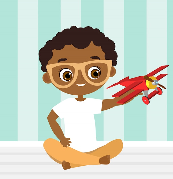 African american boy with glasses and toy plane. boy playing with airplane. Premium Vector