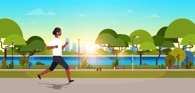 African american woman jogging outdoors modern public park Premium Vector