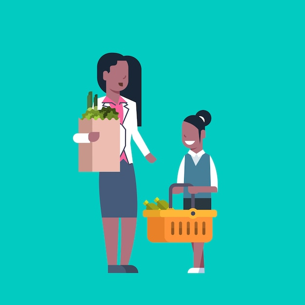 African american woman with daughter holding paper bag and shopping basket full of grocery products Premium Vector