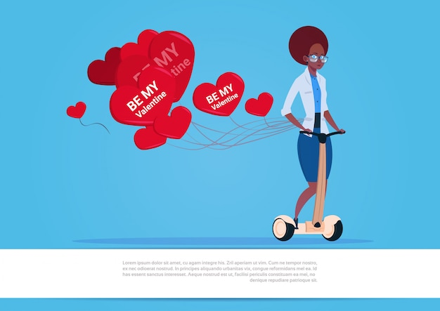 African american woman with heart shaped air balloons riding electric scooter happy valentine day concept Premium Vector