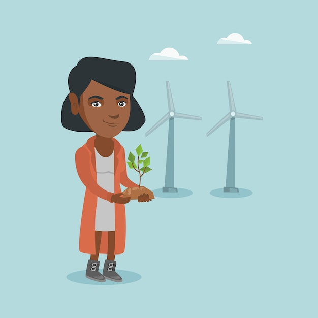African worker of wind farm holding small plant. Premium Vector