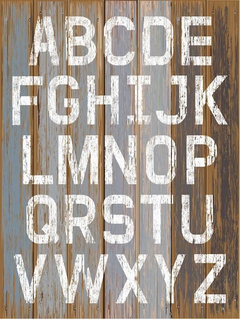 Алфавит белого цвета краской на деревянном фоне ретро цвета Premium векторы