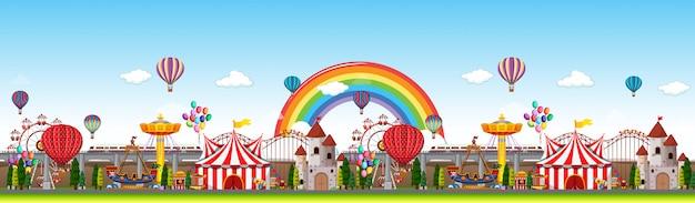 Сцена панорамы парка развлечений в дневное время с радугой в небе Бесплатные векторы