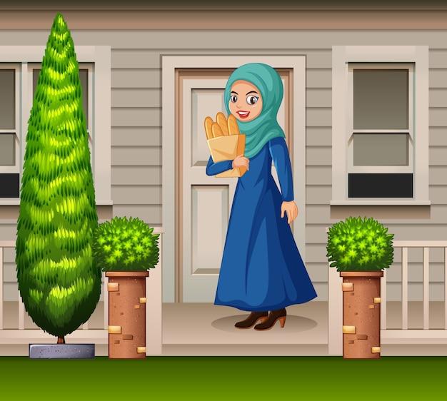 Donna araba davanti alla casa Vettore gratuito