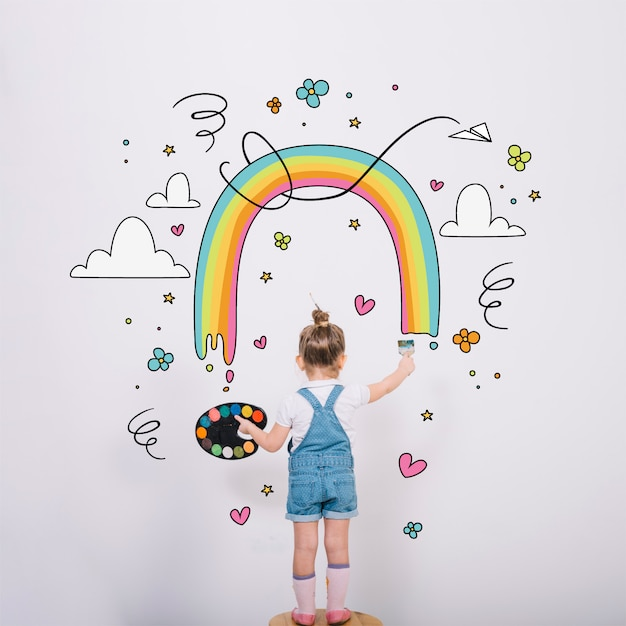 Artistic little girl painting a wonderful rainbow Free Vector