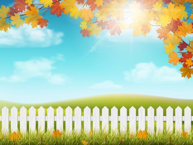 白い木の塀と秋の田園風景。カラフルな葉を持つカエデの木の枝。草や落ち葉。丘と雲と太陽と空のある牧草地の眺め。 Premiumベクター