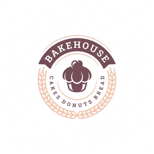 パン屋のバッジまたはラベルのレトロなイラストのカップケーキとパン屋の小麦のシルエット。 Premiumベクター