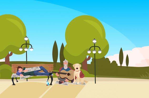 ひげを生やした男のトランプは、木製のベンチ屋外ホームレス失業コンセプト都市公園風景背景水平全長に横たわっているギターを弾いて犬酔って乞食を座っています。 Premiumベクター